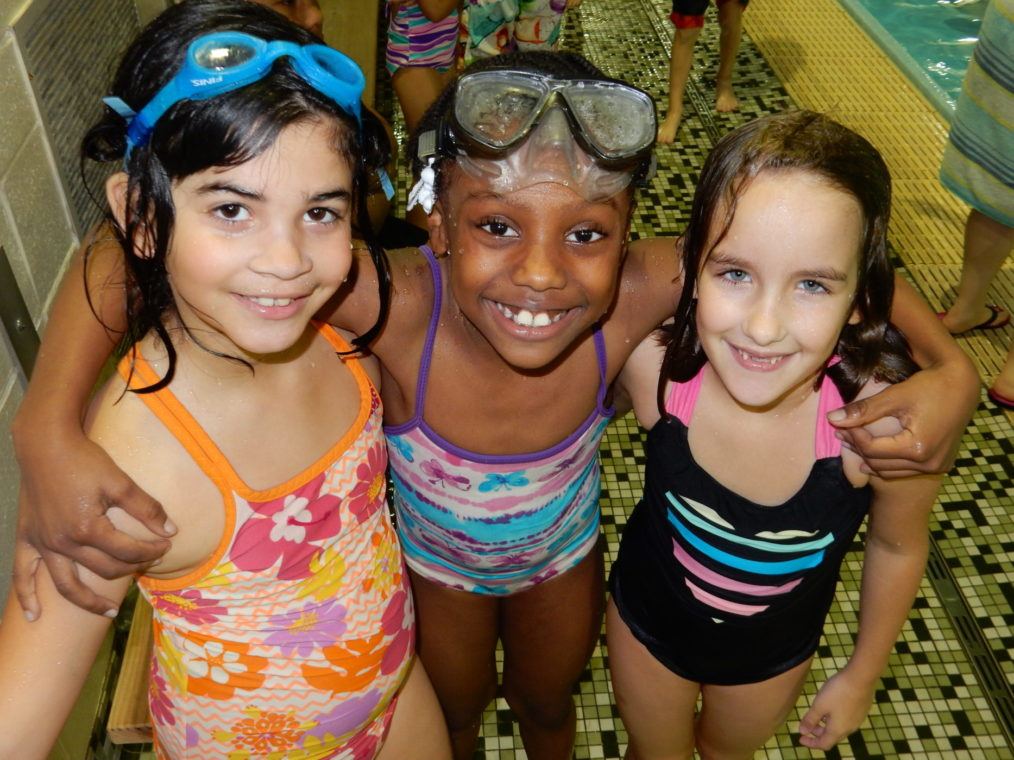 Three second grade girls stand with their arms around each other after their Evanston Swims lesson.