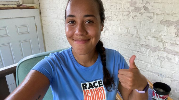 Photo of young woman in Race shirt smiling with thumbs up