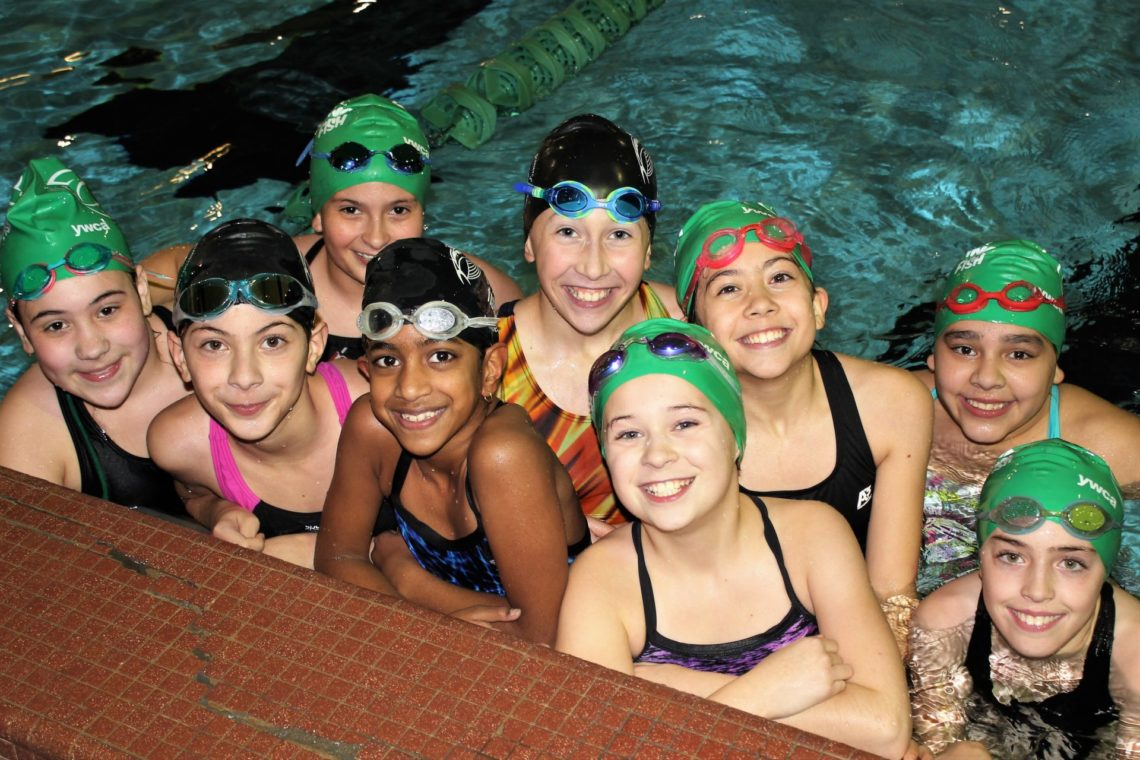 Smiling group of 10-12 year old girls on the swim team at the side of pool
