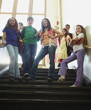 Middle school children standing together on steps in school
