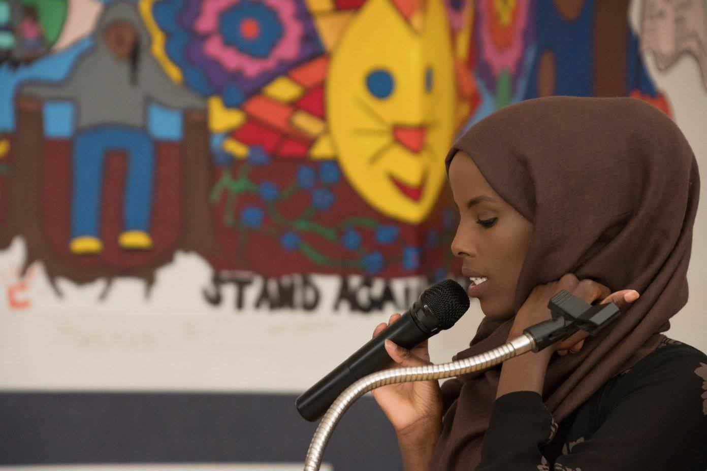 Woman in hijab speaking into microphone
