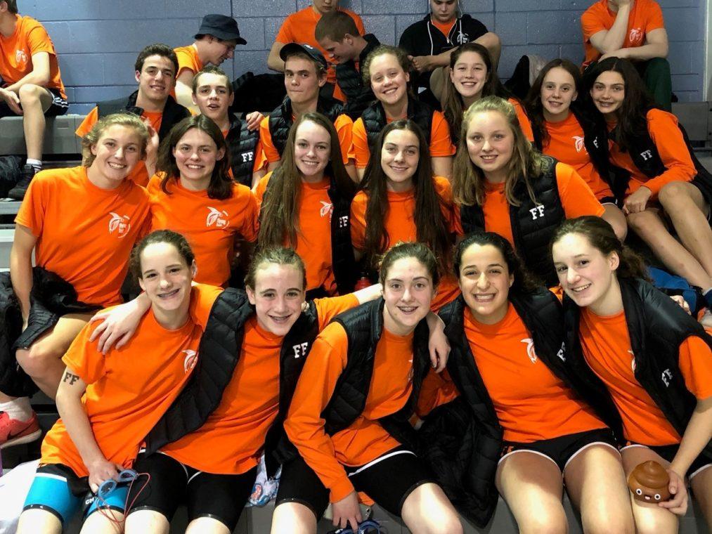 Swim team members huddles on bleachers at swim meet