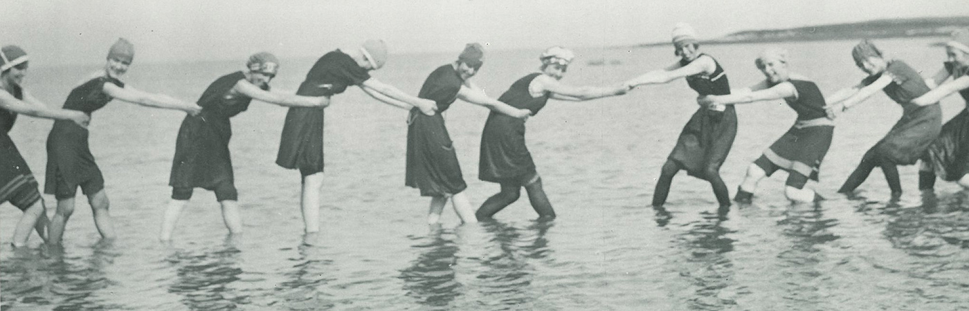 Women wading in a lake holding on to one another