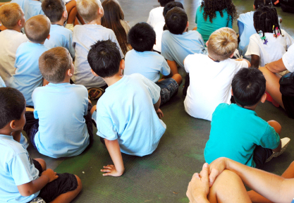 Elementary school children sitting on the floor listening to a teacher