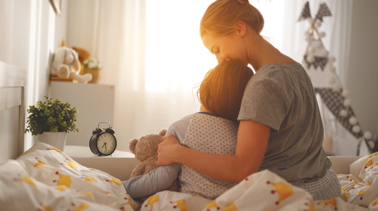 Photo of woman waking her daughter in sunny bedroom